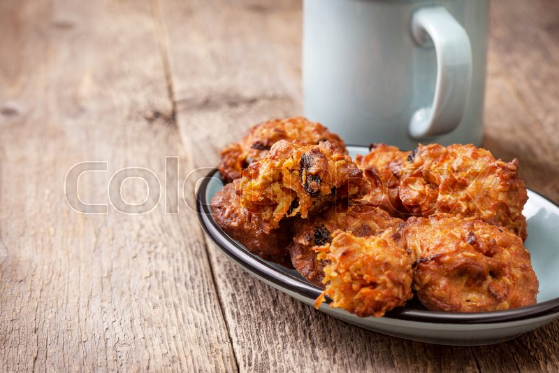 Stock image of 'carrot oatmeal cookies with raisins  on the blue plate, glass of milk  on the old wooden background'