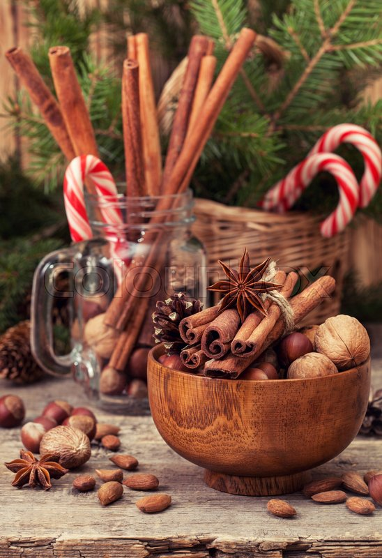 Stock image of 'Winter spices and ingredients for cooking the Christmas meal. Cinnamon sticks, hazelnuts, walnuts,  anise stars, Christmas tree branches on  old wooden background '