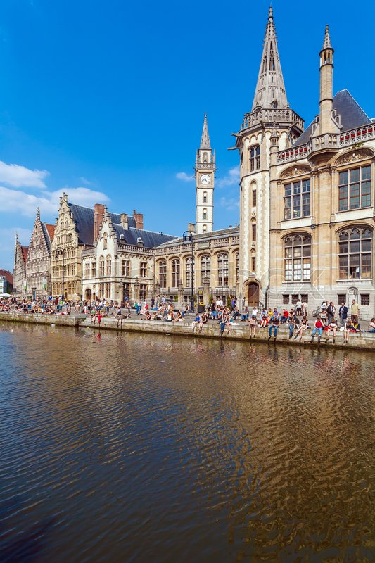 Editorial image of 'GHENT, BELGIUM - APRIL 6, 2008:  A lot of students sitting on the waterfront of river Leie along Graslei street '