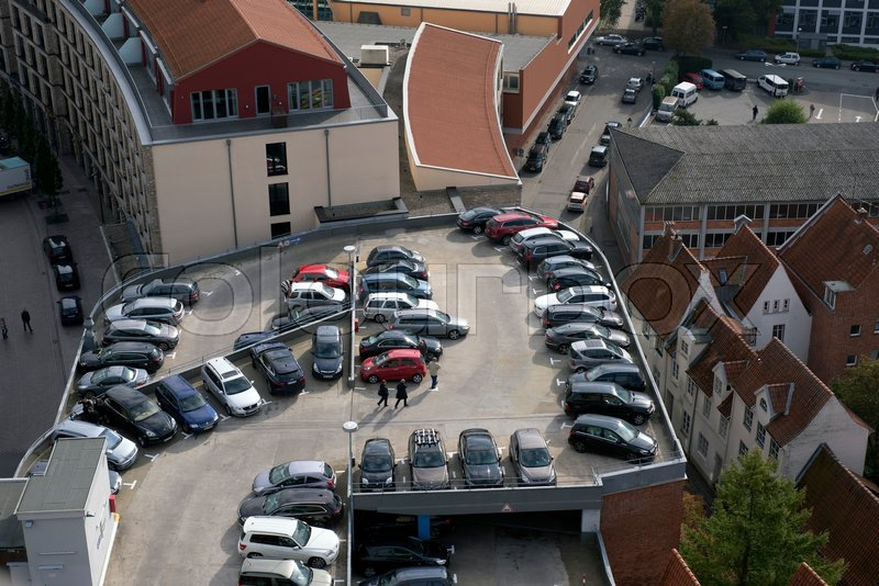 Editorial image of 'LUBECK, GERMANY – OCTOBER 13, 2016: Aerial view of Lubeck oldtown in Germany with parking garage and parked cars. Lubeck is listed by UNESCO as a World Heritage Site.'