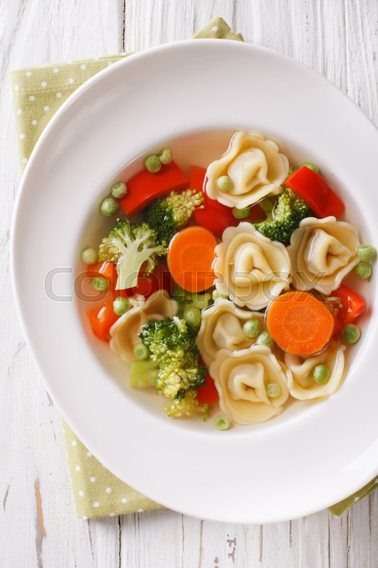 Stock image of 'Italian soup with tortellini and vegetables closeup at the plate on the table. vertical view from above\'