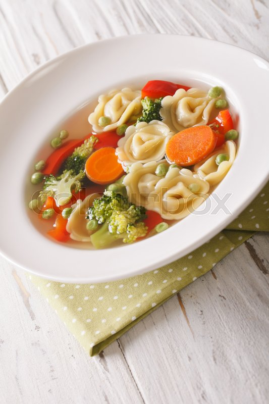 Stock image of 'tortellini soup with broccoli, peas, carrot and pepper close-up on the plate on the table. vertical\'