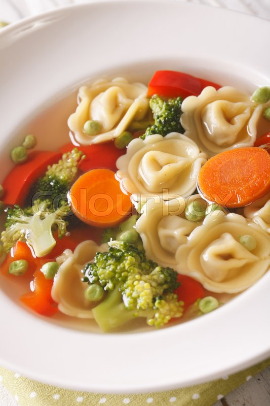 Stock image of 'Vegetable soup with tortellini in a plate close-up. vertical\'