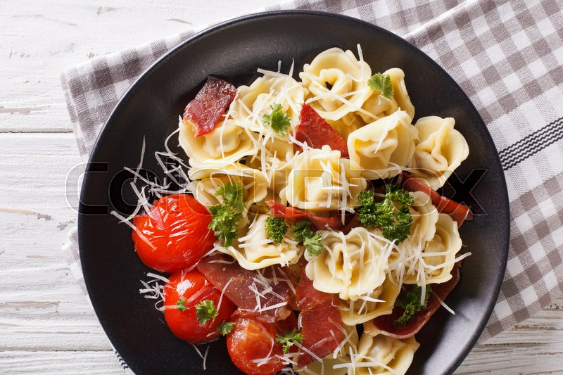 Stock image of 'Italian tortellini with prosciutto, tomatoes and parmesan close-up on a plate.  Horizontal view from above\'