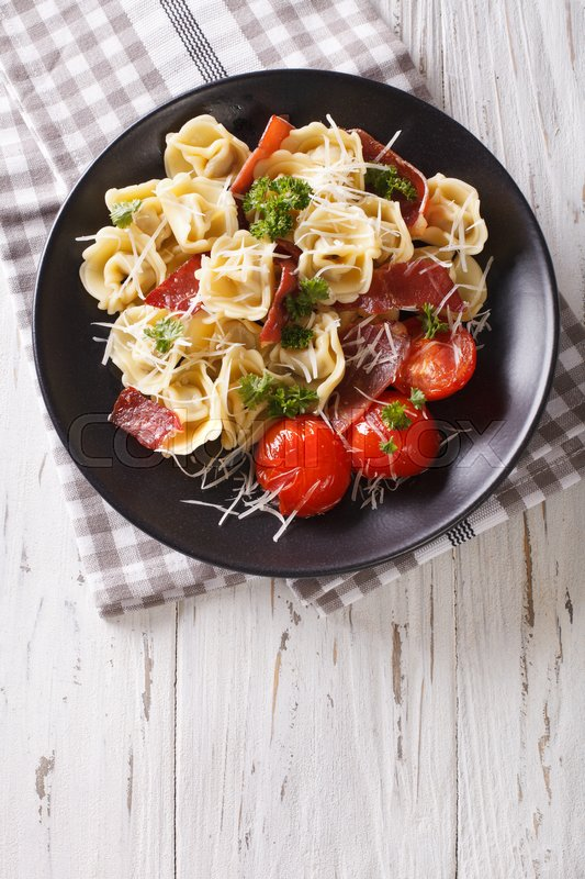 Stock image of 'Delicious tortellini with ham, tomatoes and cheese on a plate close-up. vertical view from above\'