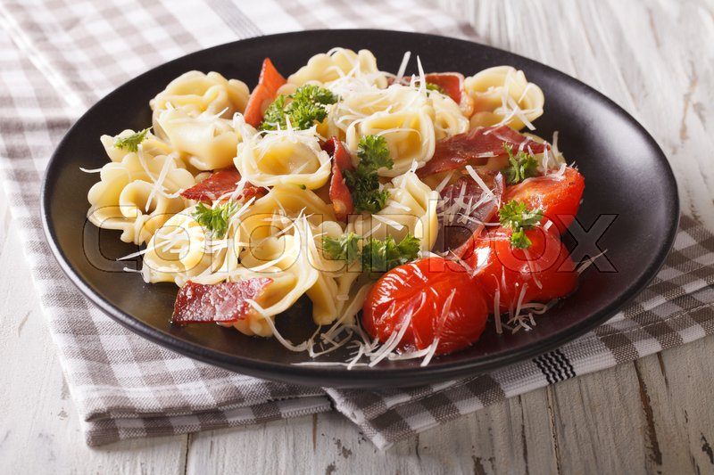 Stock image of 'Italian cuisine: tortilini with ham, tomatoes, herbs and cheese on a plate close-up. horizontal\'