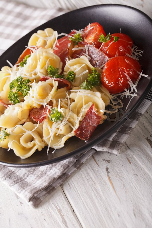 Stock image of 'Italian food: tortellini with prosciutto and parmesan close-up on a plate. vertical \'
