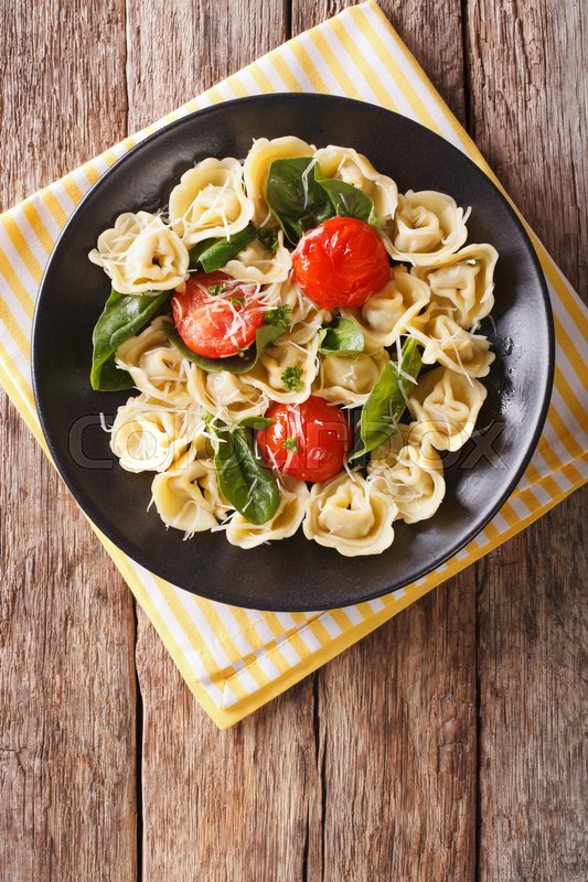 Stock image of 'Freshly cooked tortellini with spinach and parmesan close-up on a plate. Vertical view from above\'