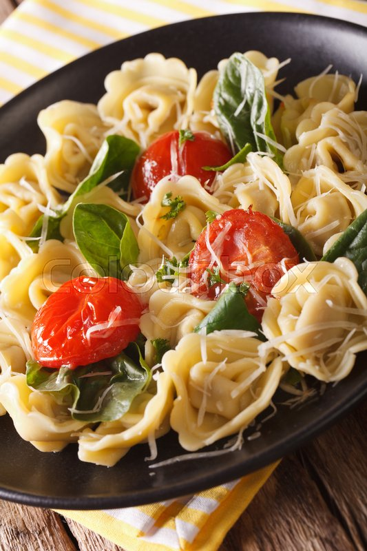 Stock image of 'Italian tortellini with spinach, tomatoes and parmesan close-up on a plate. vertical\'