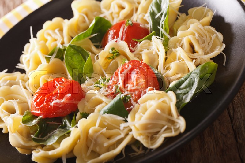 Stock image of 'Italian tortellini with spinach, tomatoes and parmesan close-up on a plate. Horizontal\'