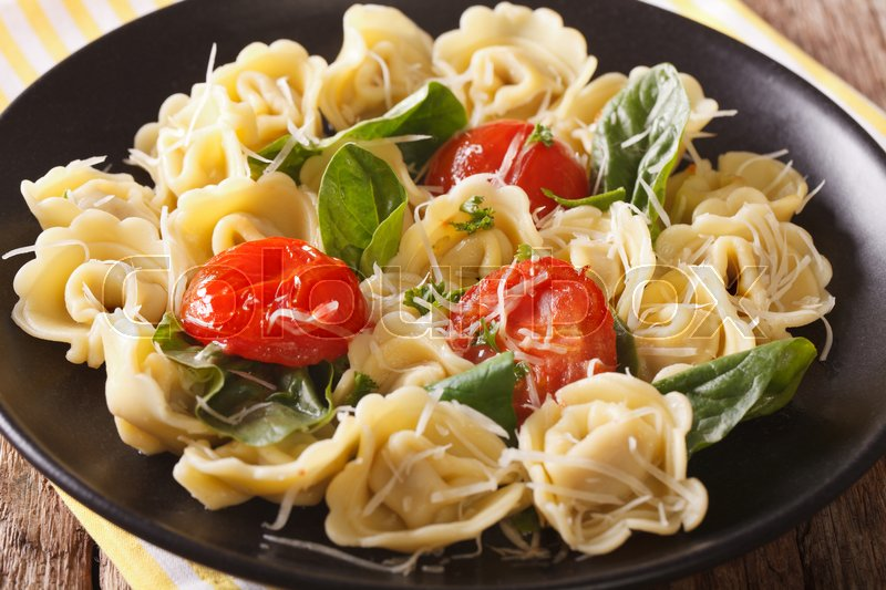 Stock image of 'Italian cuisine: tortellini with spinach, tomatoes and parmesan close-up on a plate. horizontal\'