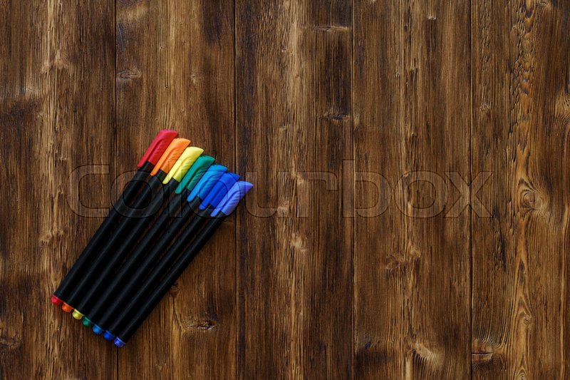Stock image of 'Lots of assorted rainbow colors marker pens with copyspace, on dark wooden background'