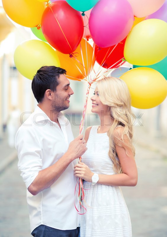 Stock image of 'summer holidays, celebration and dating concept - couple with colorful balloons in the city'