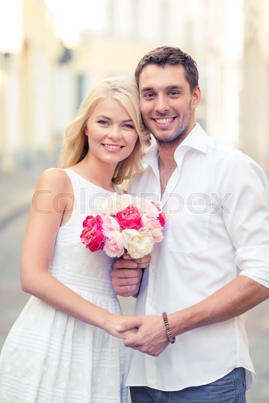 Stock image of 'summer holidays, love, relationship and dating concept - couple with bouquet of flowers in the city'