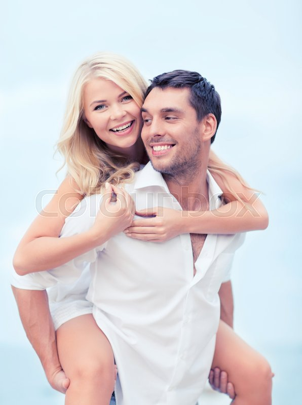 Stock image of 'summer holiday, vacation, dating and tourism concept - happy couple having fun on the beach'