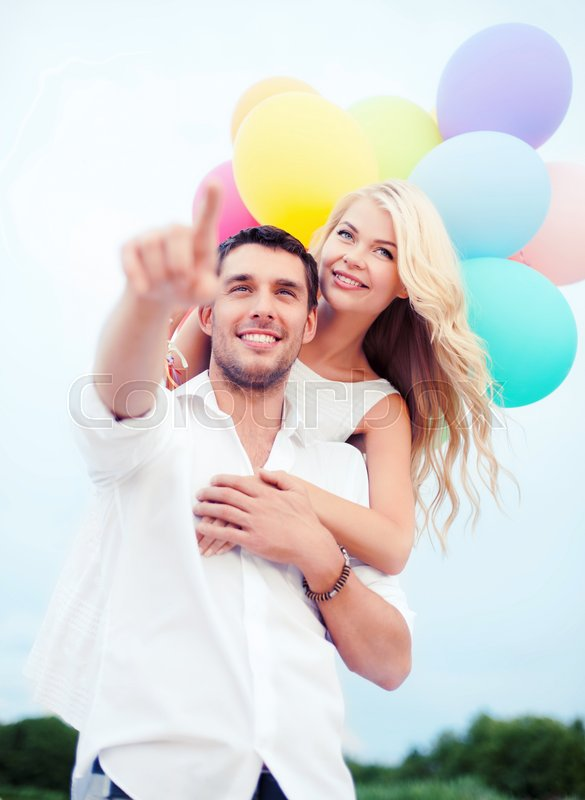 Stock image of 'summer holidays, celebration and dating concept - couple with colorful balloons at sea side'
