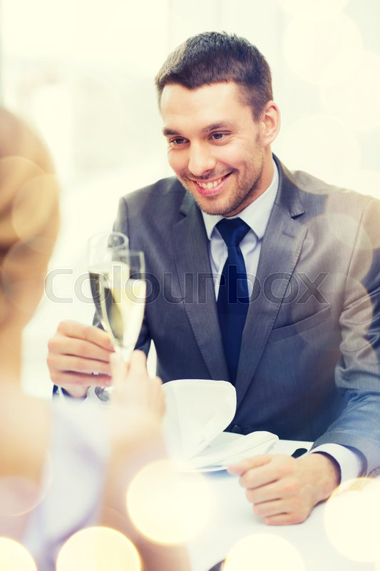 Stock image of 'restaurant, couple and holiday concept - smiling man with glass of champagne looking at wife or girlfriend at restaurant'