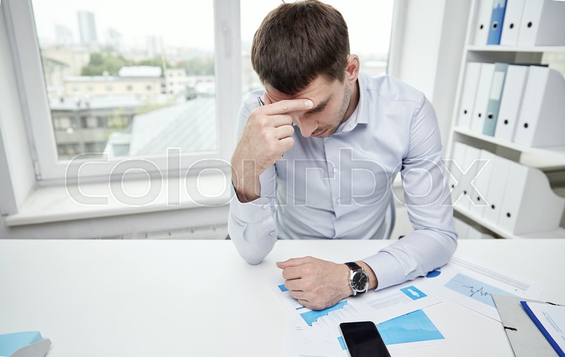 Stock image of 'business, people, paperwork and deadline concept - stressed businessman with smartphone, papers and charts sitting at table in office'