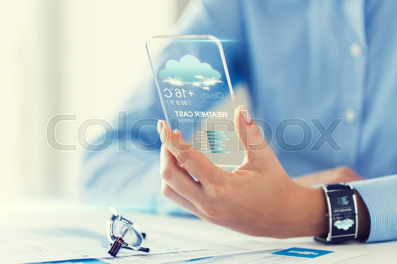 Stock image of 'technology, application, weather, forecast and people concept - close up of woman hand holding transparent smartphone with cloud icon and air temperature on screen at office'