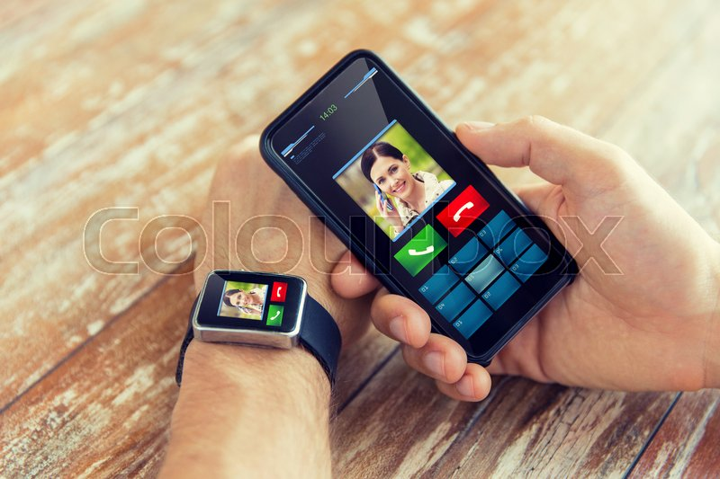 Stock image of 'business, technology and people concept - close up of male hand holding smart phone and wearing smart watch with incoming call interface on screen'