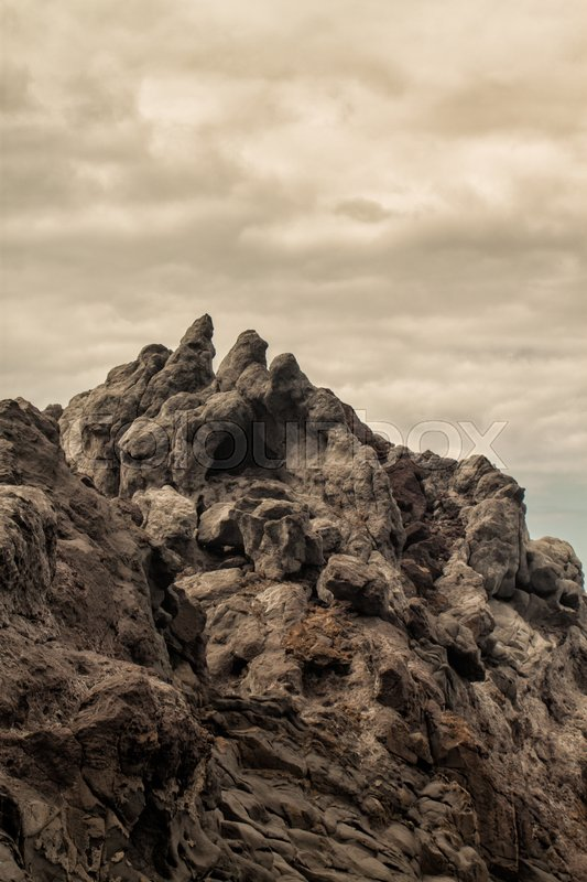 Stock image of 'volcanic cliffs on cloud day'