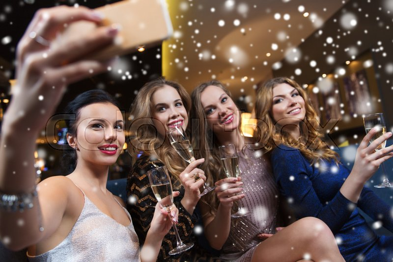 Stock image of 'celebration, friends, bachelorette party, technology and holidays concept - happy women with champagne glasses and smartphone taking selfie at night club'