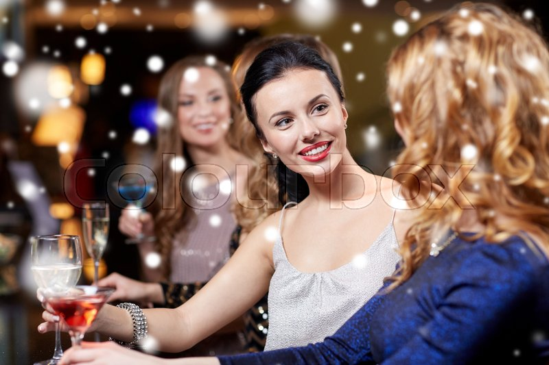 Stock image of 'new year party, christmas, winter holidays and people concept - happy women drinking champagne and cocktails at night club over snow'