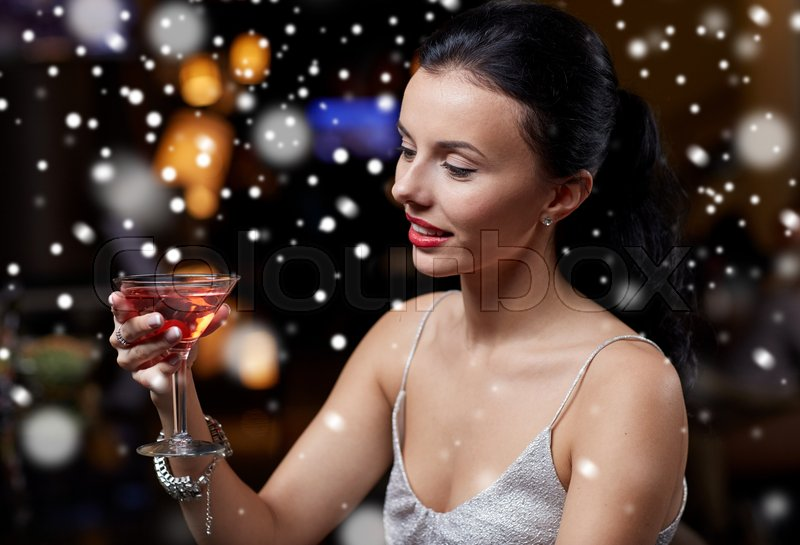 Stock image of 'new year party, christmas, winter holidays and people concept - glamorous woman with cocktail at night club or bar over snow'
