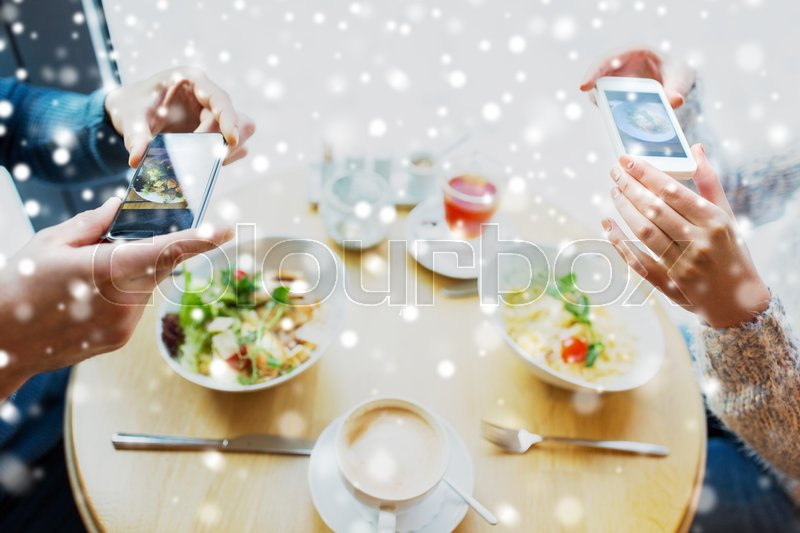 Stock image of 'people, technology, eating and dating concept - close up of couple with smartphones picturing food at cafe or restaurant'