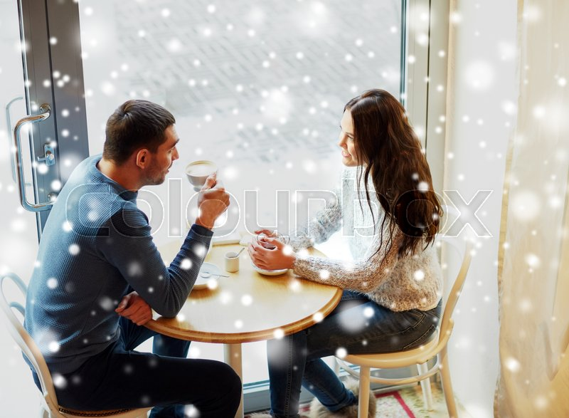 Stock image of 'people, communication and dating concept - happy couple drinking tea and coffee at cafe'