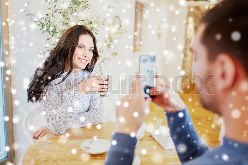 Stock image of 'people, communication and dating concept - man with smartphone taking picture of woman drinking tea at cafe or restaurant'
