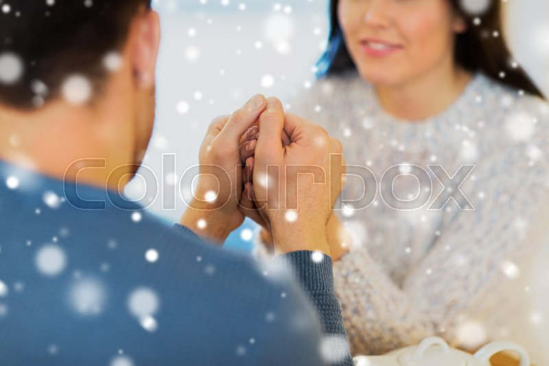Stock image of 'people, love, romance and dating concept - close up of couple drinking tea and holding hands at cafe or restaurant'