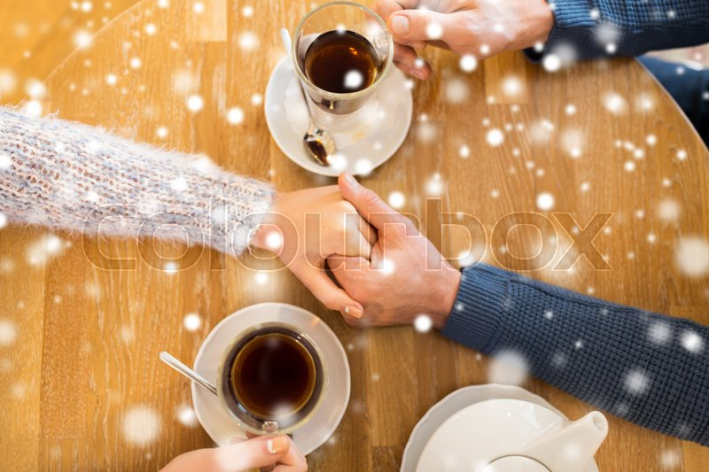 Stock image of 'people, love, romance and dating concept - close up of happy couple drinking tea and holding hands at cafe or restaurant'