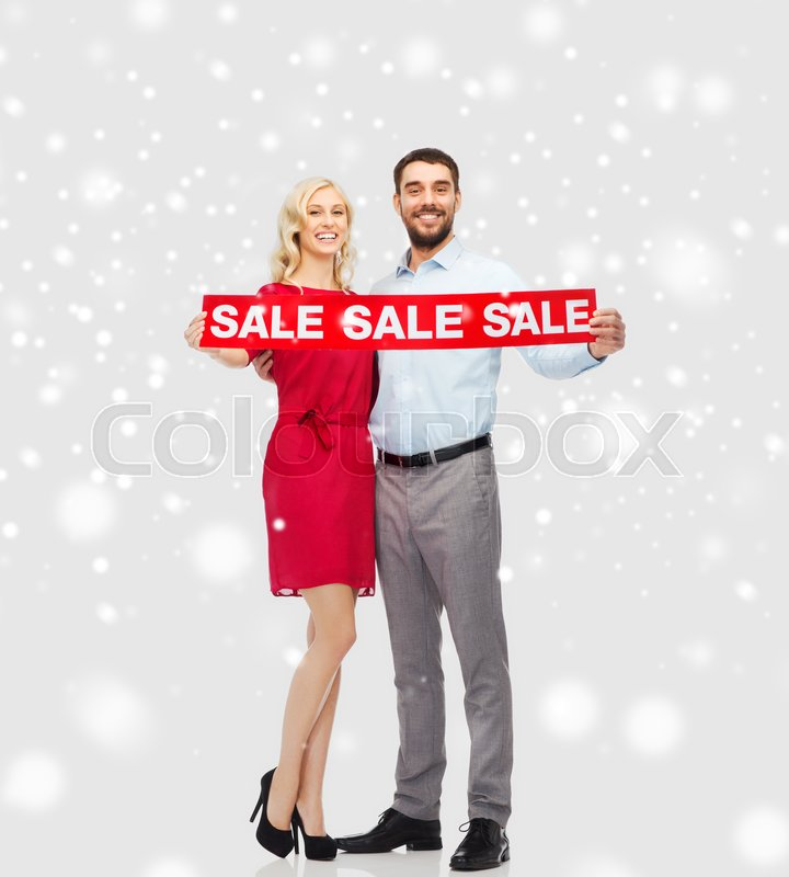 Stock image of 'people, christmas, shopping, winter and holidays concept - happy couple with red sale sign over snow background'
