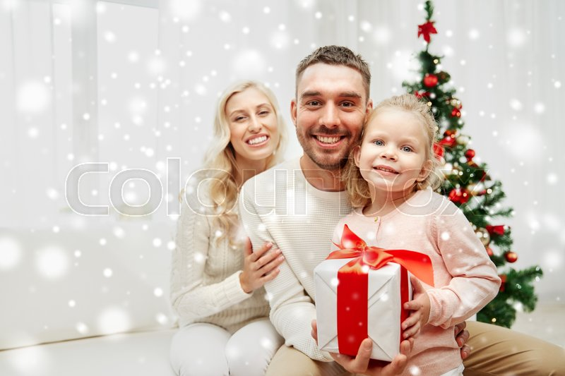 Stock image of 'family, christmas, holidays and people concept - happy mother, father and little daughter with gift box sitting on sofa at home'