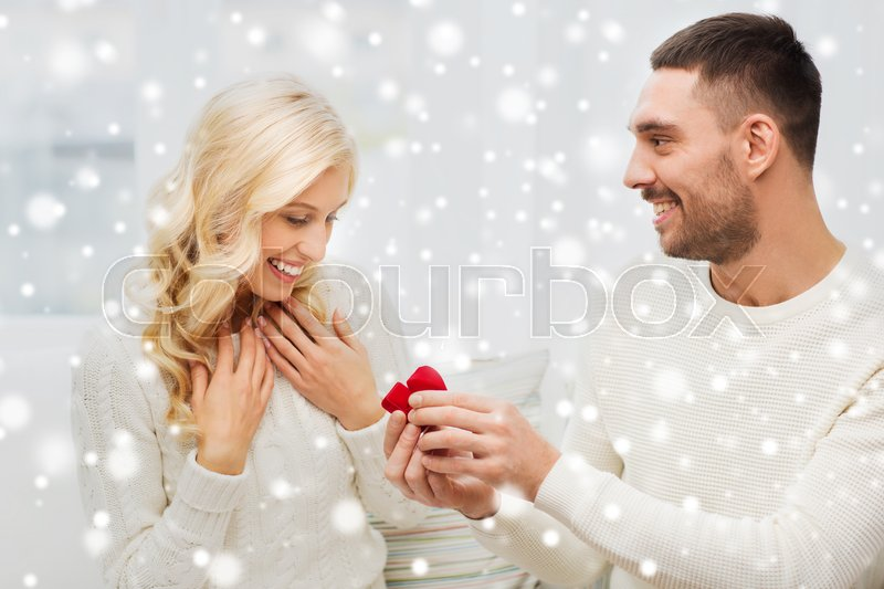 Stock image of 'love, couple, relationship, proposal and holidays concept - happy man giving engagement ring in little red gift box to woman at home'