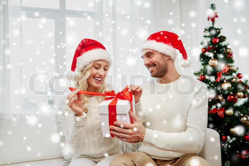 Stock image of 'christmas, holidays and people concept - happy couple in santa hats with gift box sitting on sofa at home'