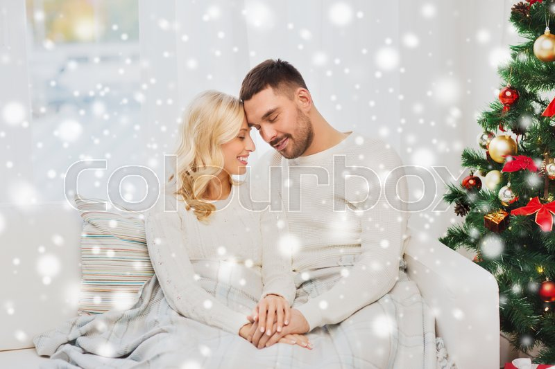 Stock image of 'family, love, christmas, winter holidays and people concept - happy couple covered with plaid sitting on sofa at home'