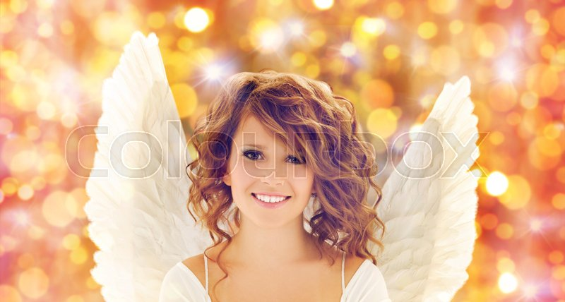 Stock image of 'people, holidays, christmas and party concept - happy young woman or teen girl with angel wings over lights background'