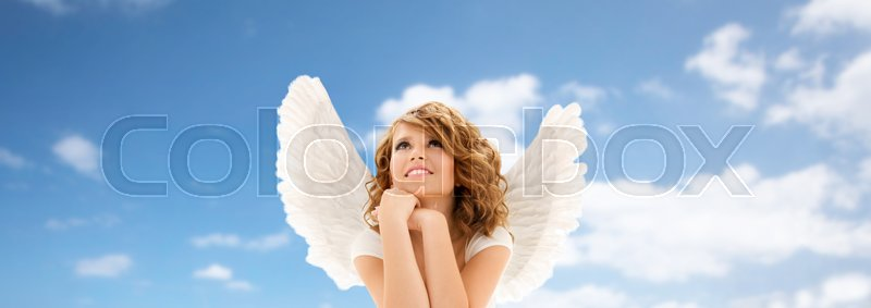 Stock image of 'people, holidays, christmas and religious concept - happy young woman or teen girl with angel wings over blue sky and clouds background'
