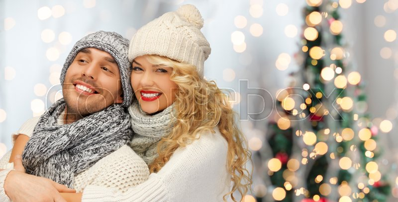 Stock image of 'people, christmas, holidays and new year concept - happy family couple in winter clothes hugging over lights background'