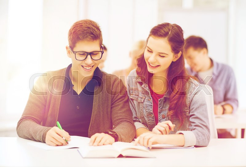Stock image of 'education, school and people concept - two teenagers with notebooks and book at school'