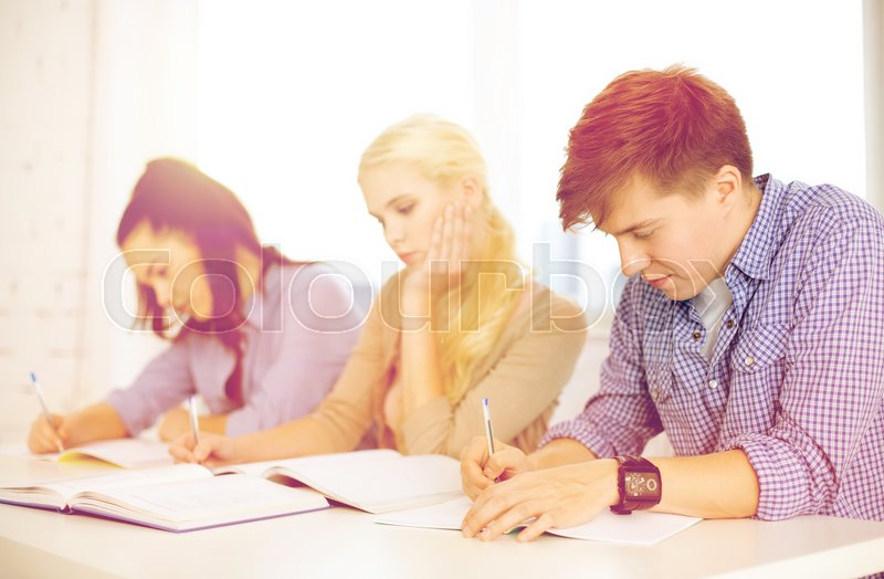 Stock image of 'school and education concept - group of tired students with notebooks at school'