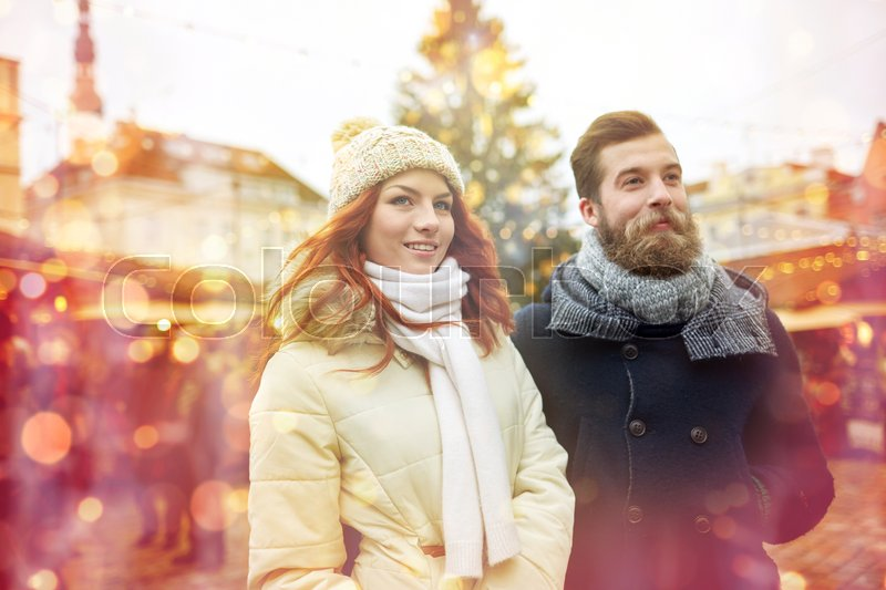 Stock image of 'holidays, winter, christmas, tourism and people concept - happy couple in warm clothes walking in old town'