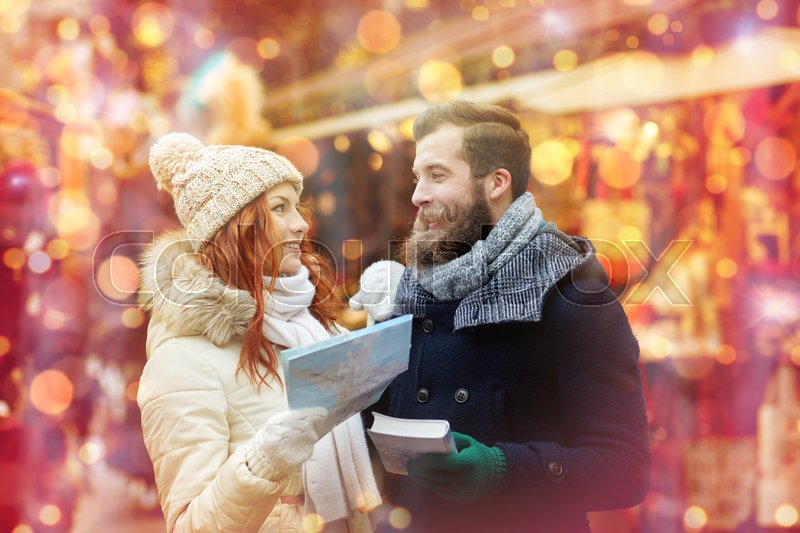 Stock image of 'holidays, winter, christmas, tourism and people concept - happy couple in warm clothes with map and city guide in old town'