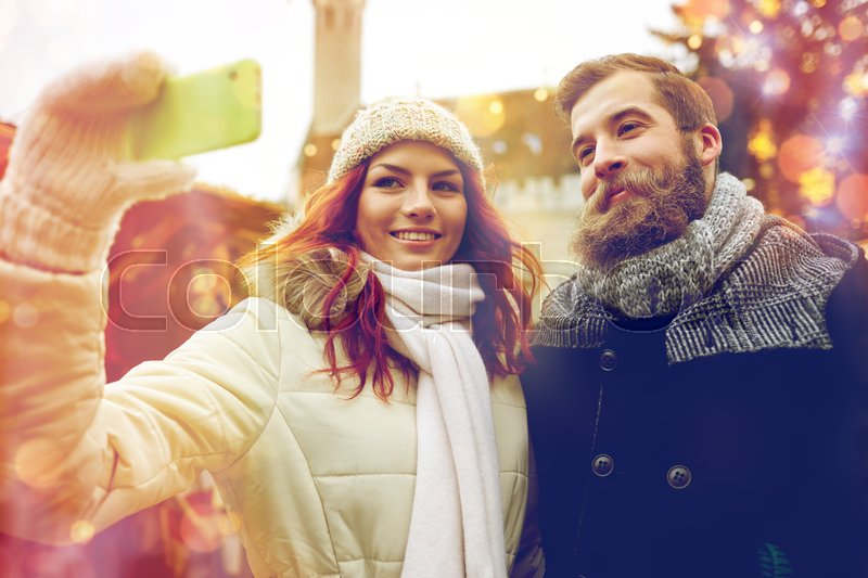 Stock image of 'holidays, winter, christmas, technology and people concept - happy couple of tourists in warm clothes taking selfie with smartphone in old town'