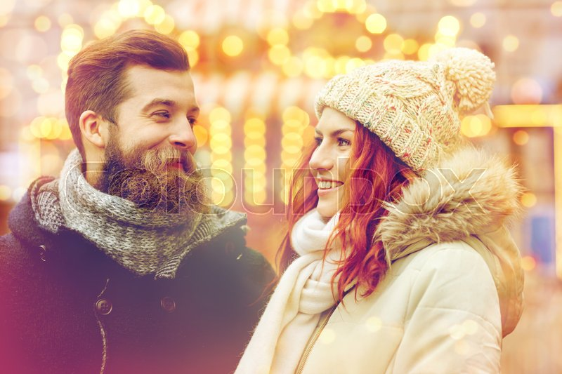 Stock image of 'holidays, winter, christmas and people concept - happy couple in warm clothes walking in old town'