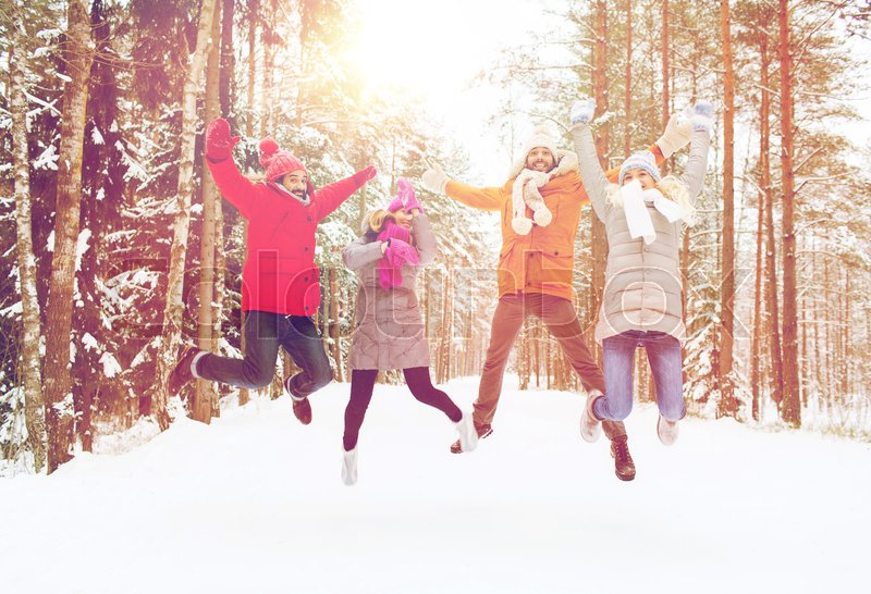 Stock image of 'leisure, season, friendship and people concept - group of smiling men and women having fun and jumping in winter forest'