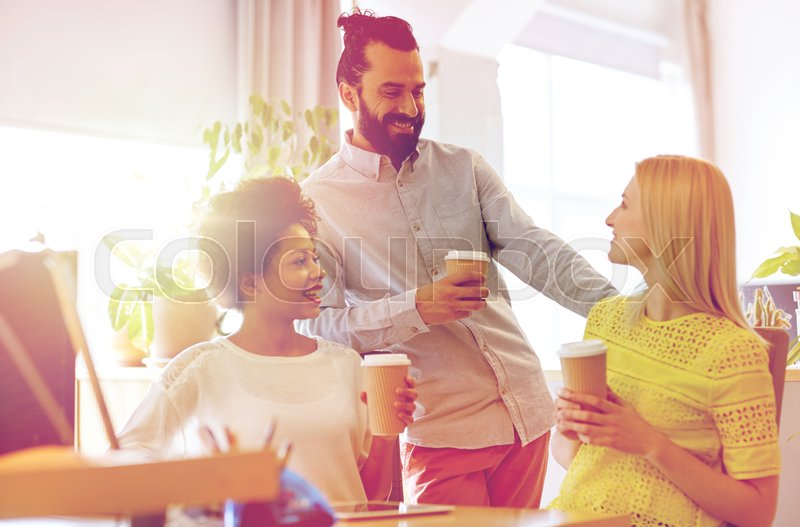 Stock image of 'business, startup, people and teamwork concept - happy creative team drinking coffee in office'