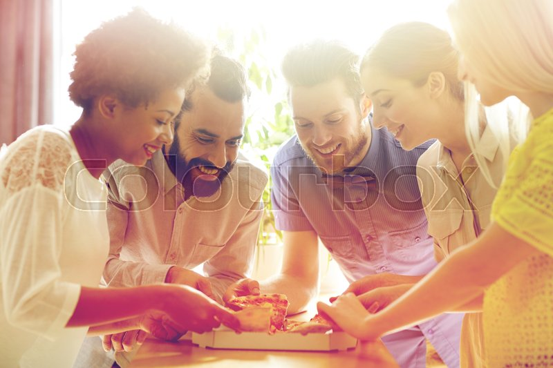 Stock image of 'business, food, lunch and people concept - happy business team or friends eating pizza in office'